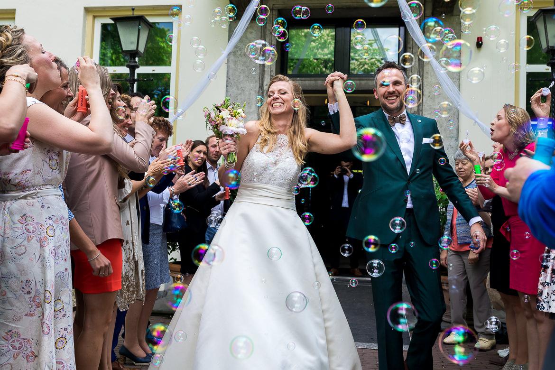 Bruidspaar loopt door erehaag heen met bellenblaas
