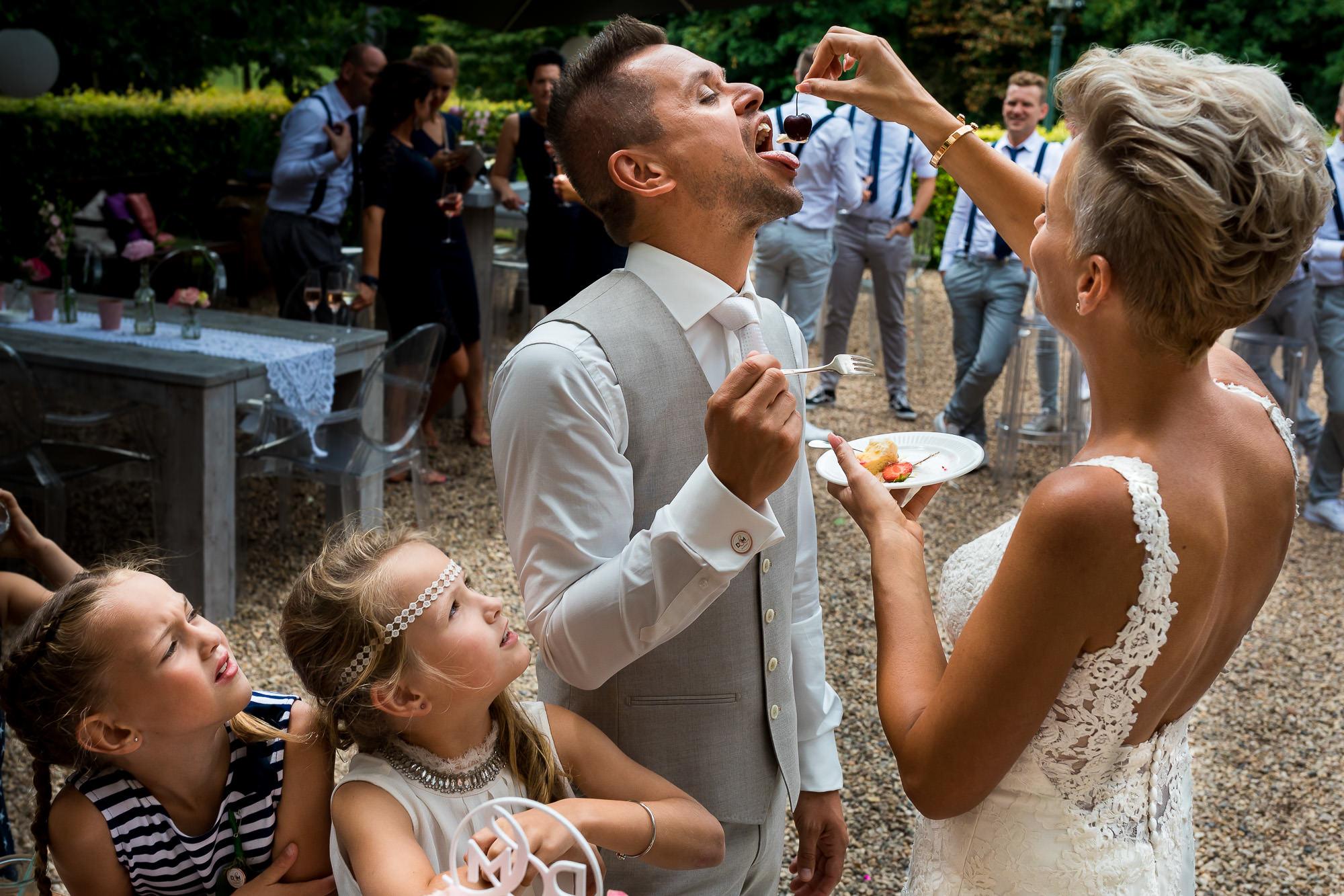 Kinderen kijken mee hoe het echtpaar elkaar taart voert