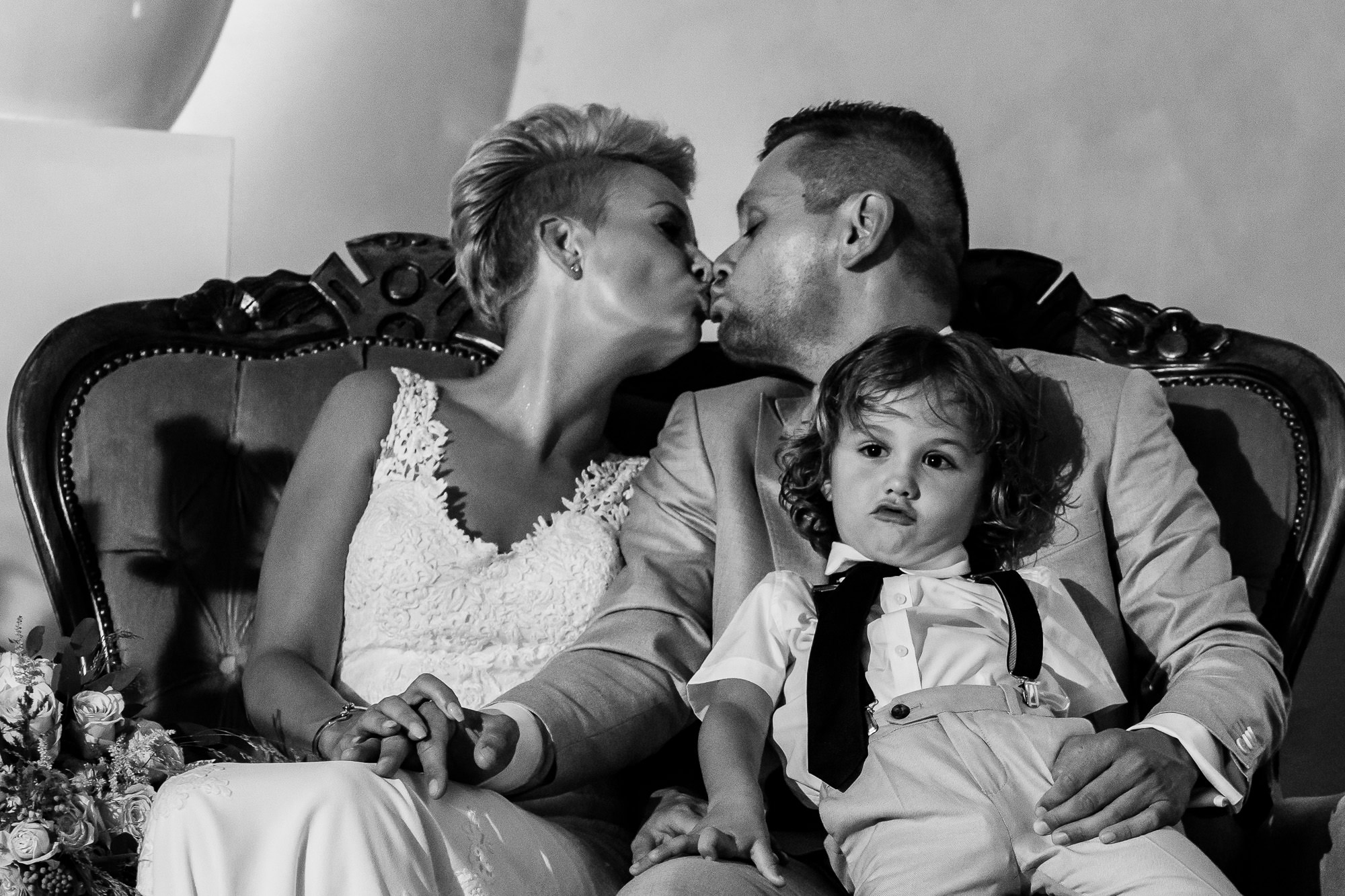 Kindje trekt een gekkenbek terwijl papa en mama kussen