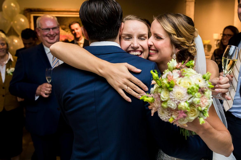 Zus van de bruid knuffelt bruidspaar