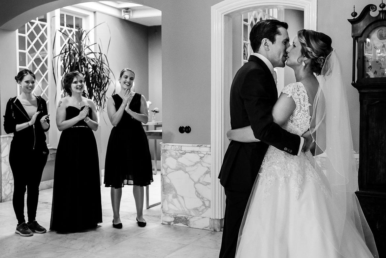 Vrienden kijken naar bruidspaar terwijl zij elkaar kussen