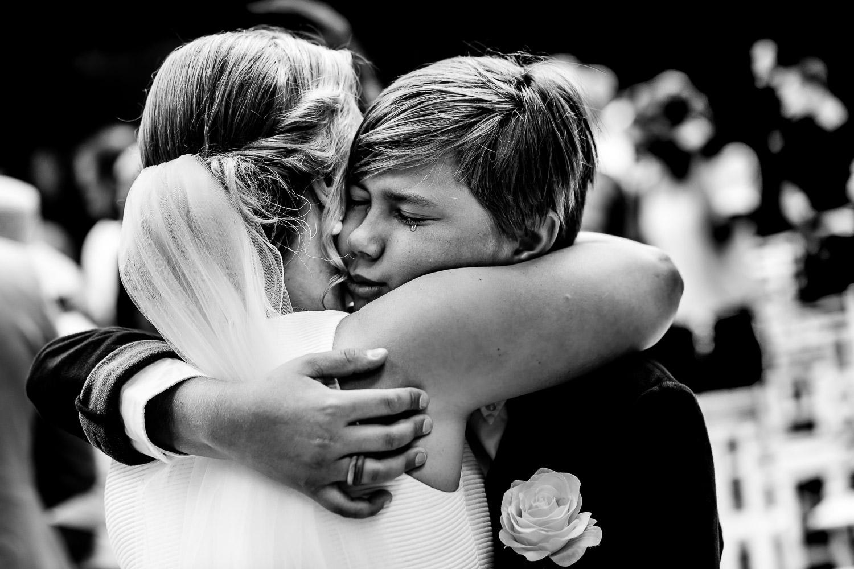 Kindje knuffelt bruid met tranen in zijn ogen
