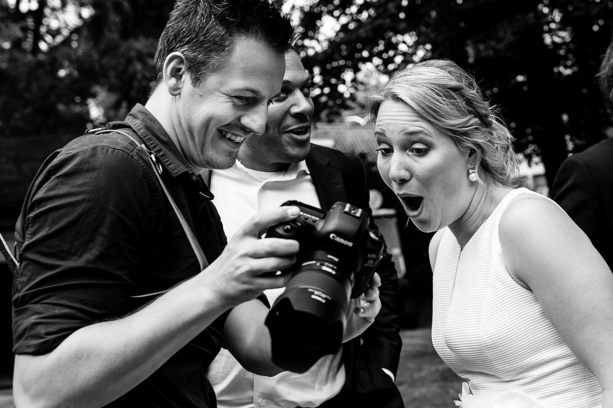 Bruidsfotograaf laat resultaat zien aan de bruid op de camera