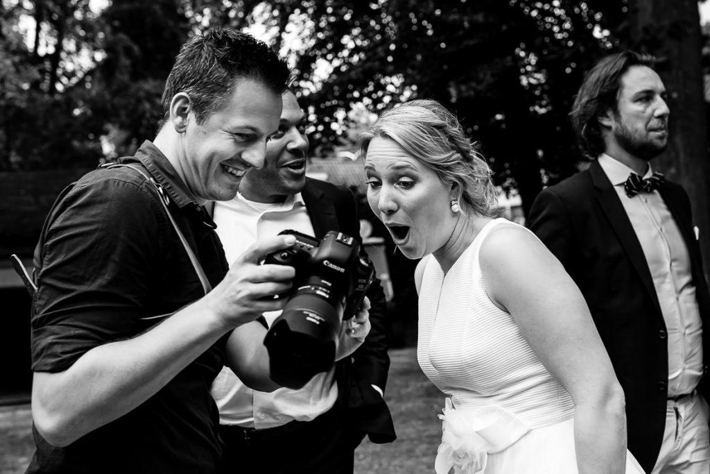 Bruidsfotograaf laat foto zien aan bruid achterop de camera