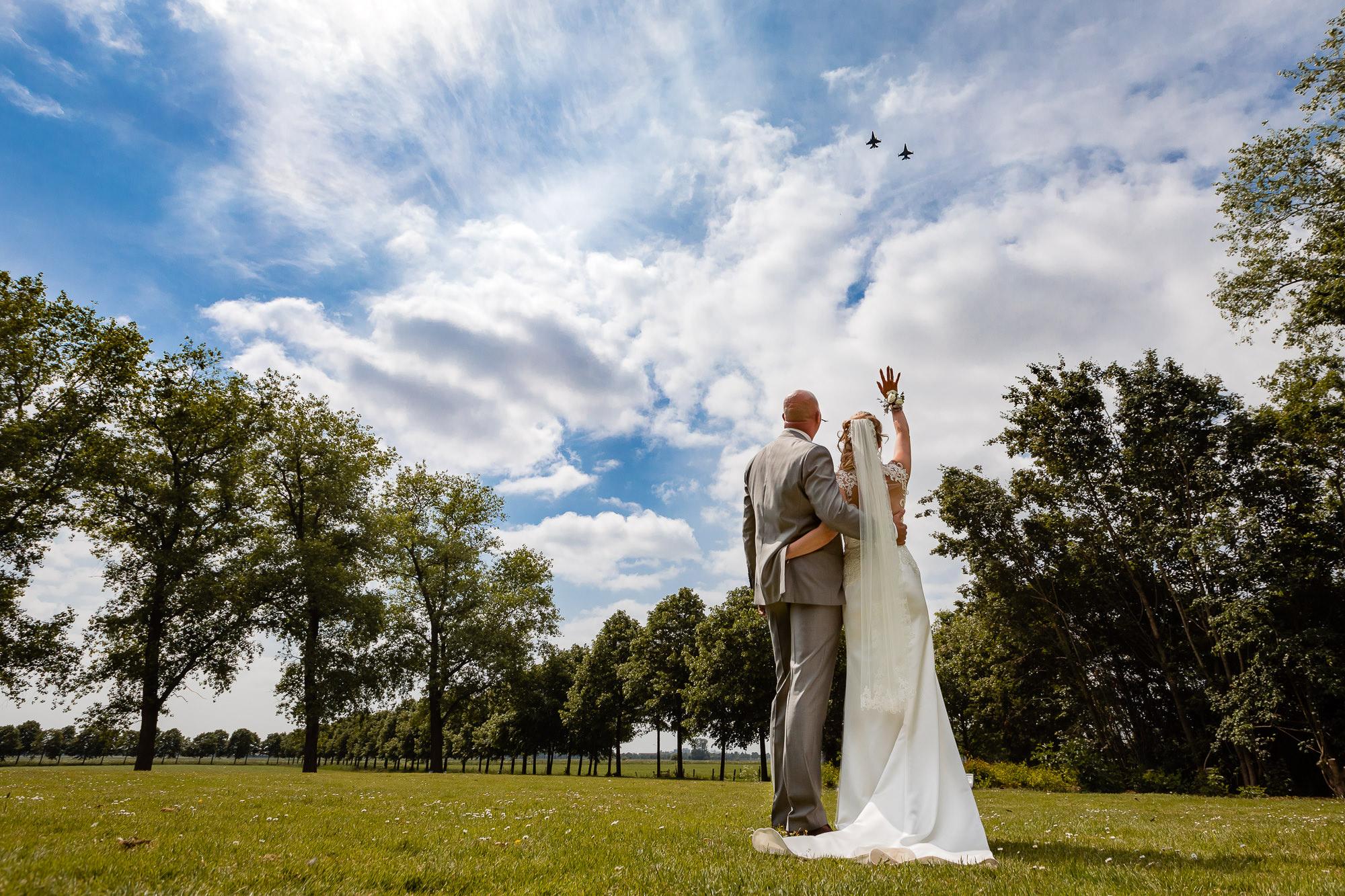Bruidspaar zwaait naar een f16 fly by in oss