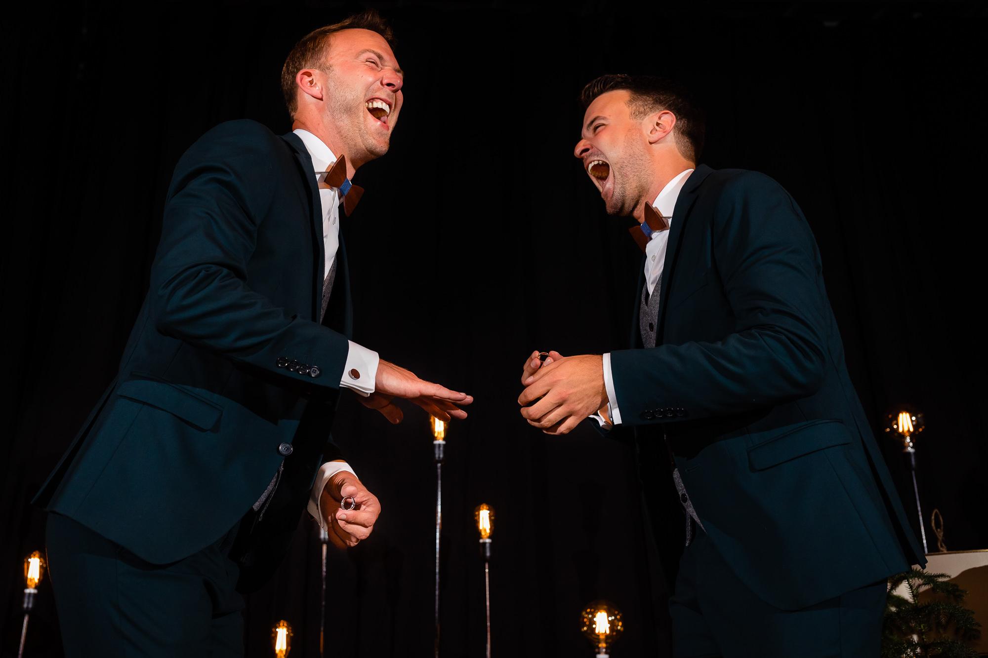 Bruidegommen aan het lachen tijdens het aandoen van de ringen