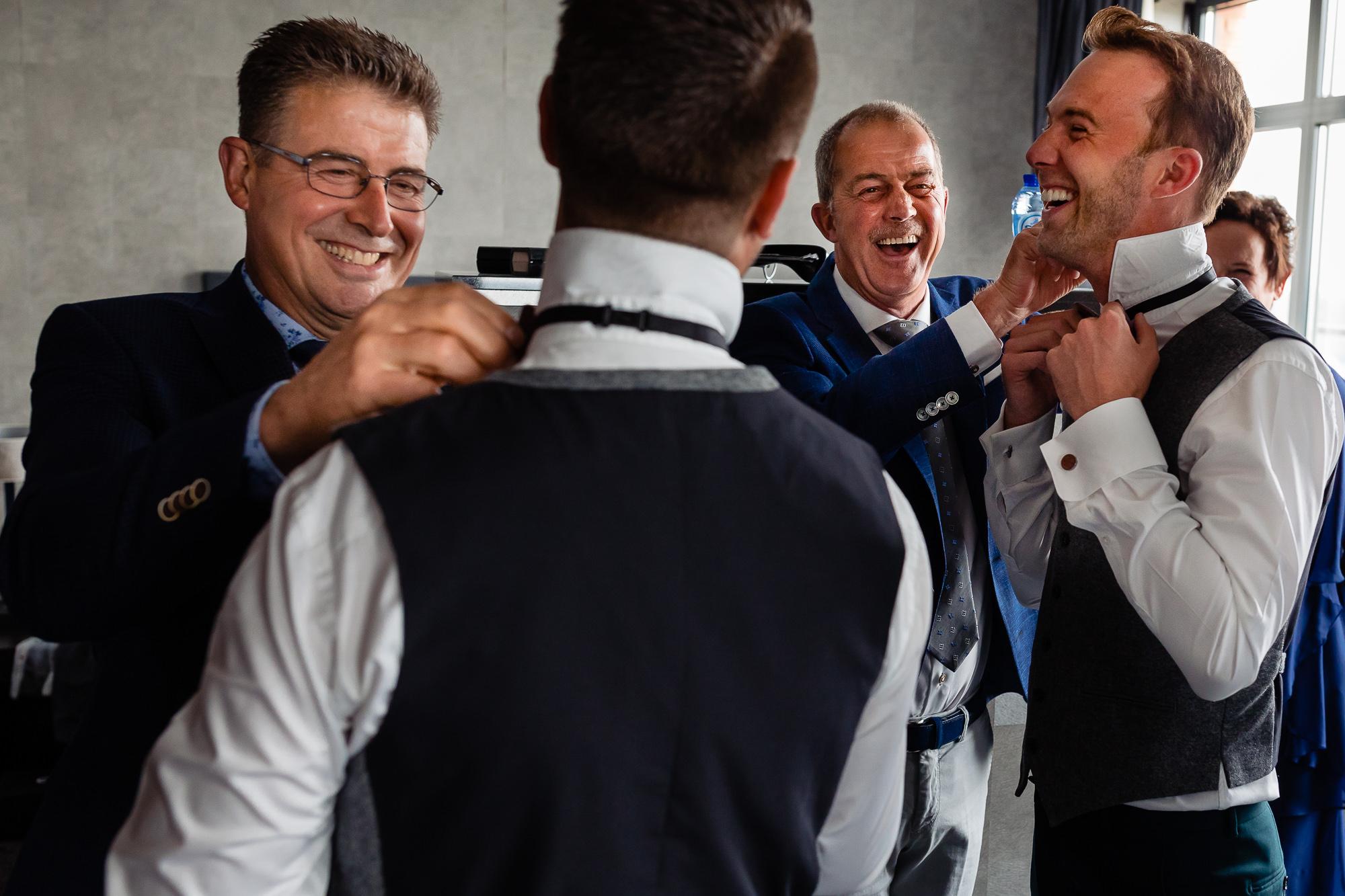 Vaders van de bruidegommen helpen beiden mee met het aankleden van hun zoons