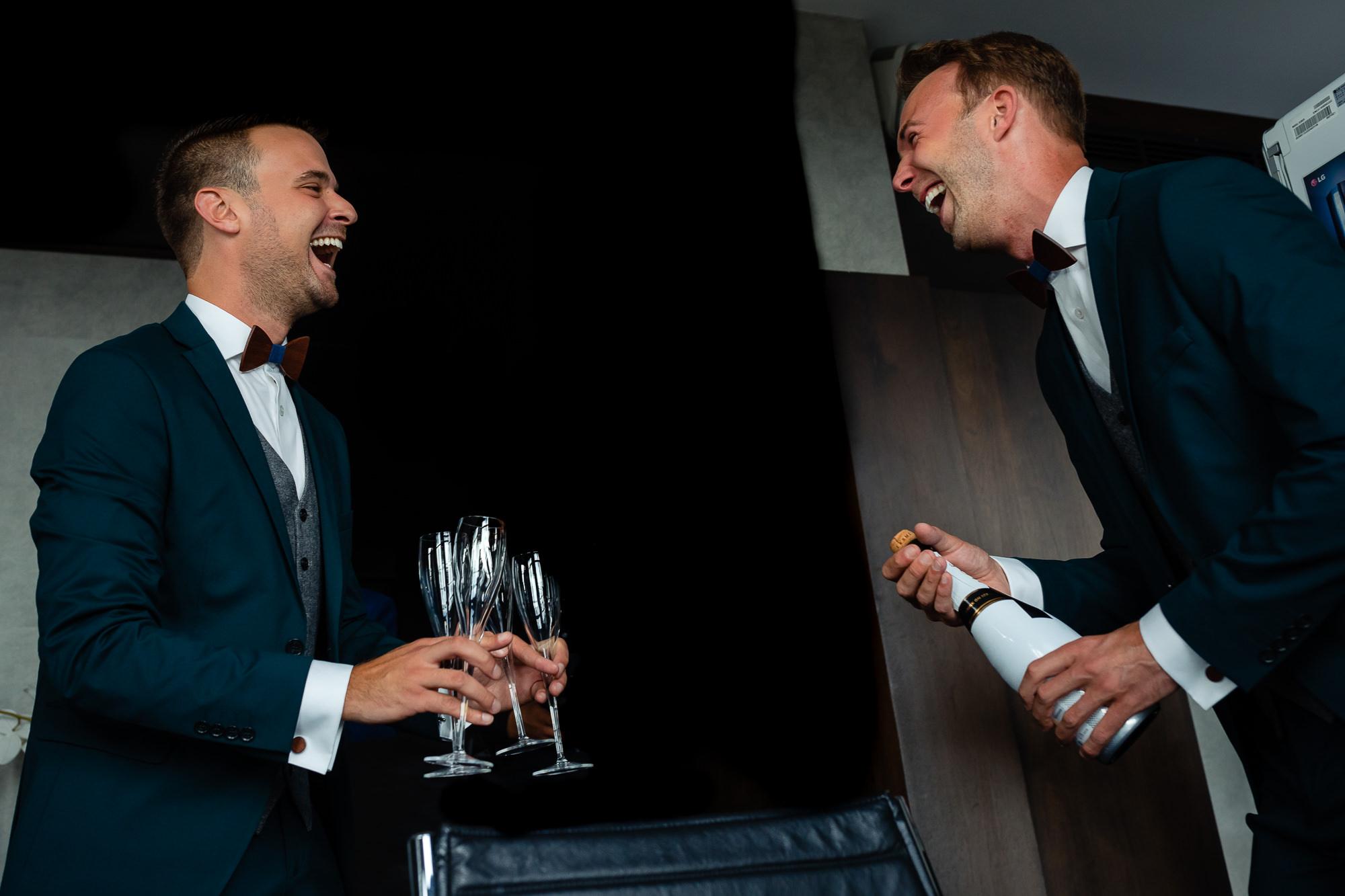 Bruidegommen trekken een fles champagne open