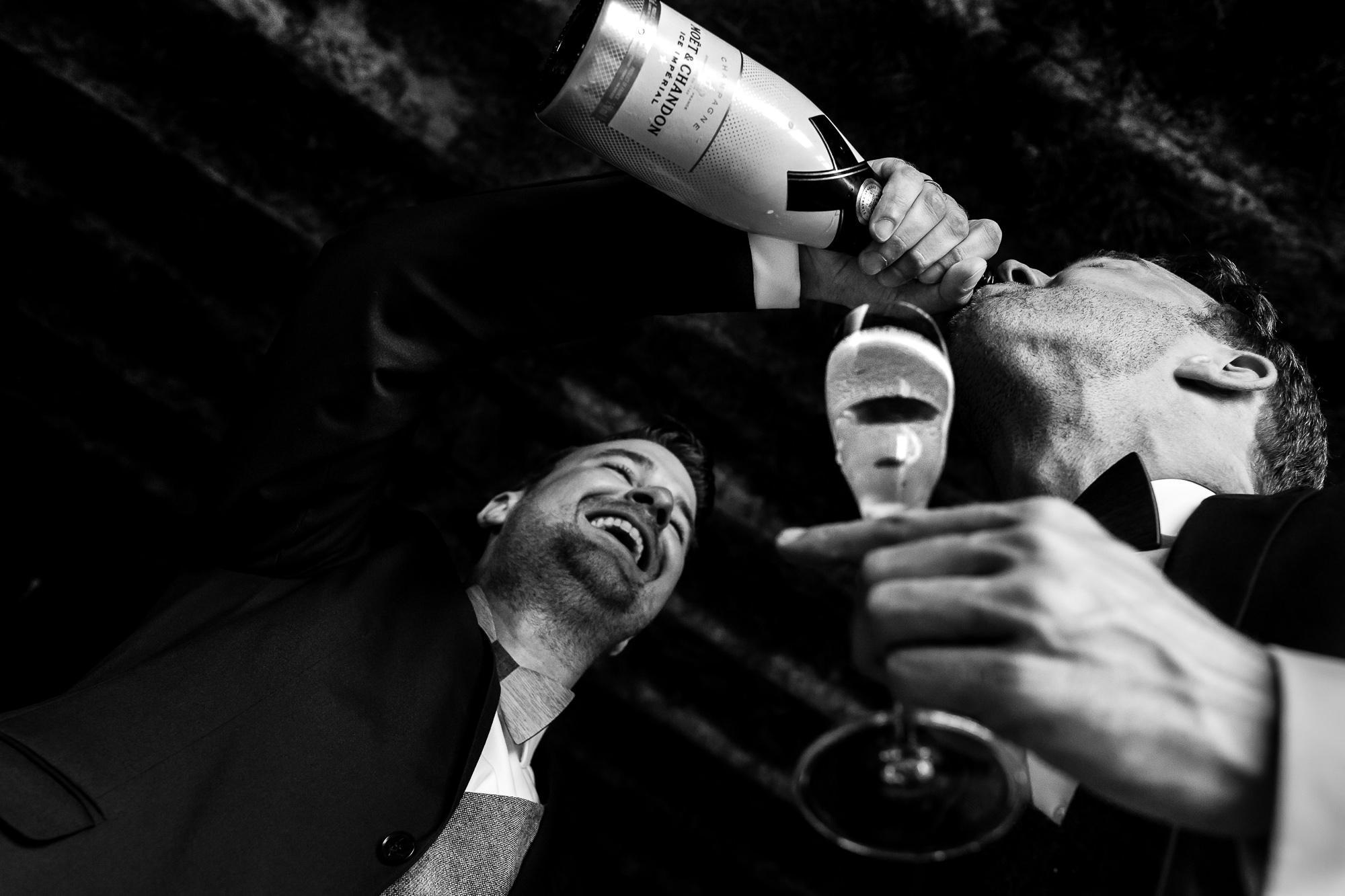 Bruidegom schenkt champagne vanuit de fles bij zijn aanstaande