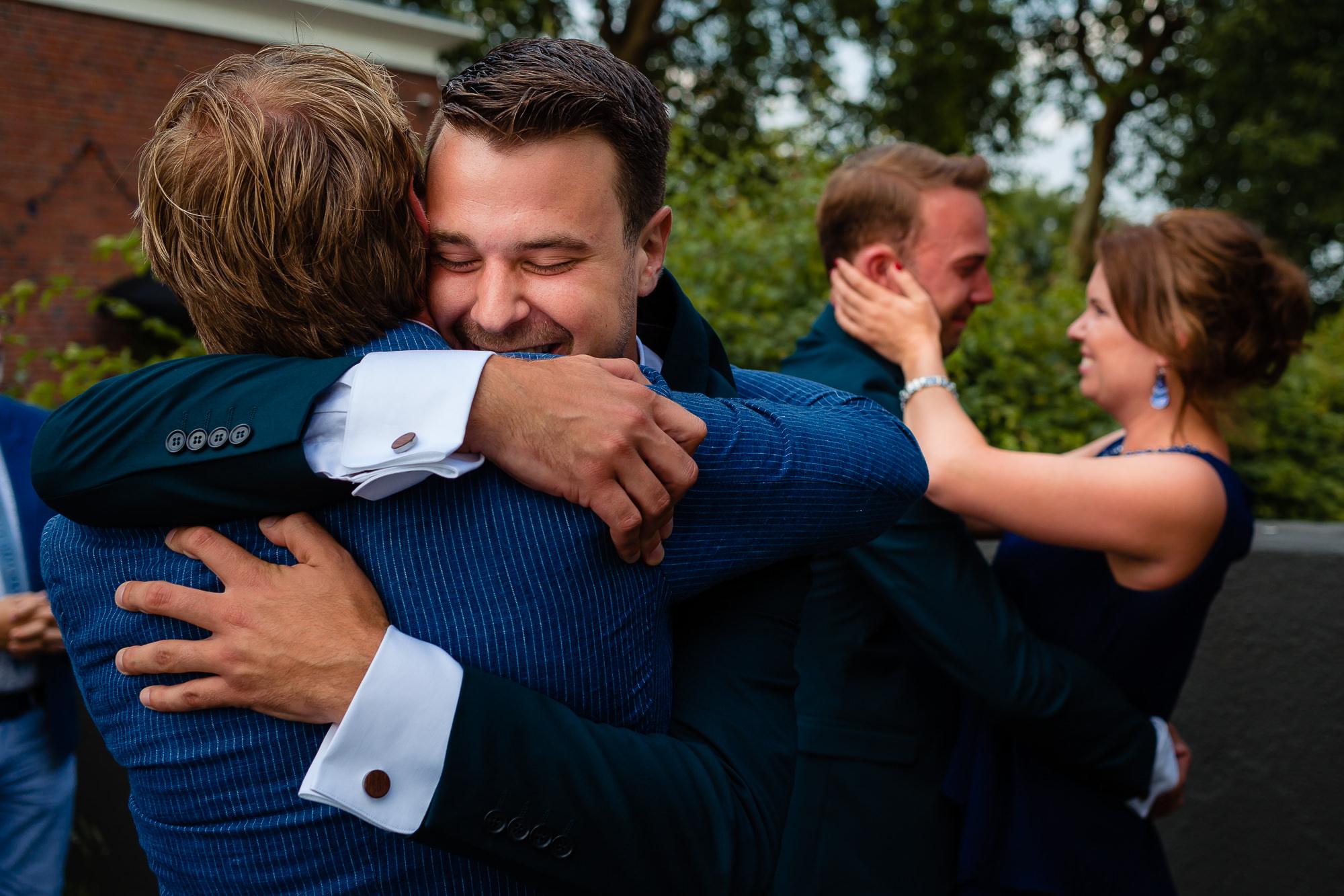 Bruidegommen worden beiden geëmotioneerd geknuffeld