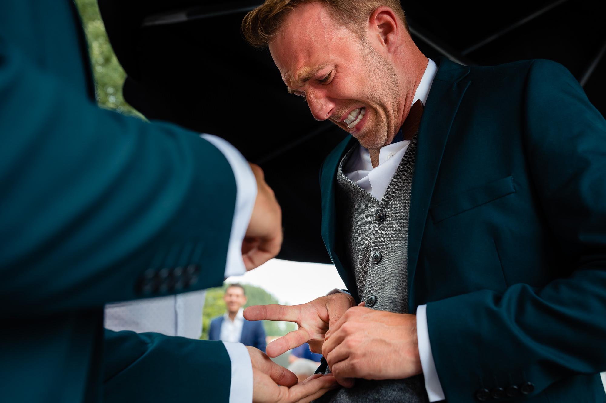 Bruidegom probeert zijn trouwring af te doen en kijkt hier heel moeilijk bij
