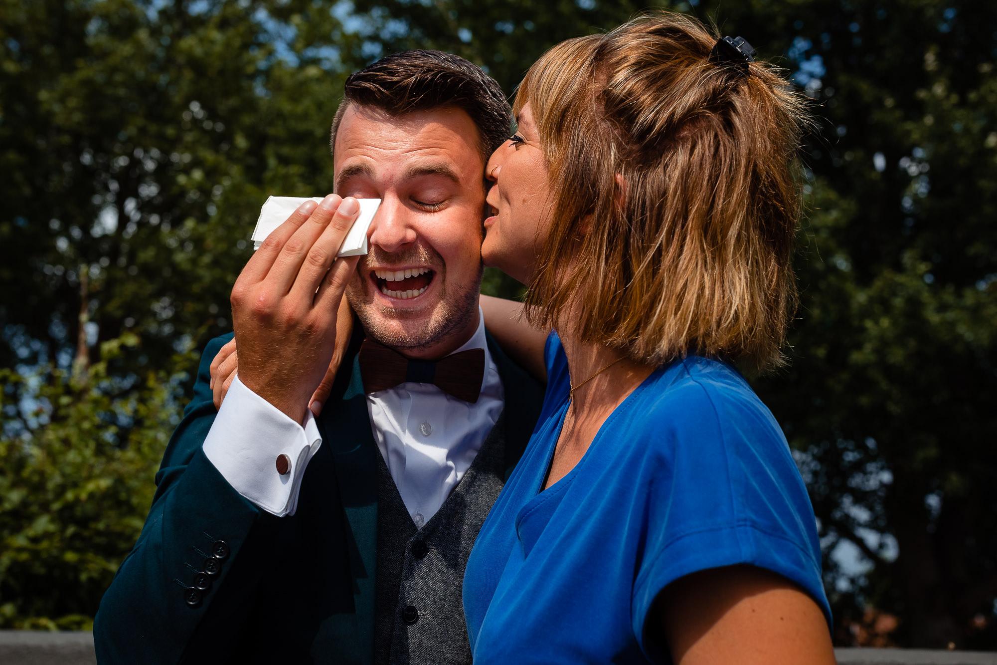 Vriendin kust de bruidegom terwijl hij een traan weg veegt