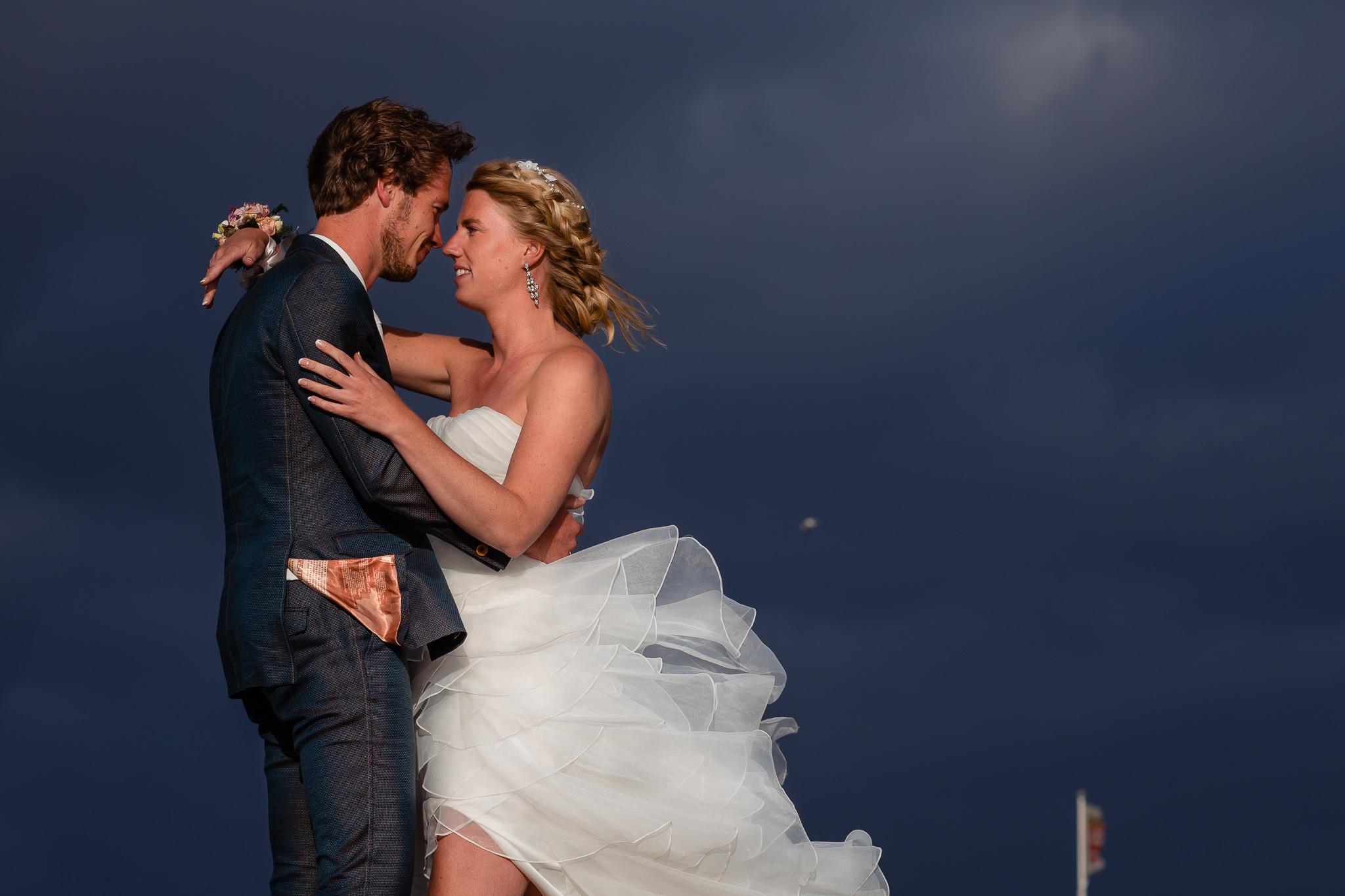 Bruidspaar tijdens de zonsondergang met dreigende lucht op de achtergrond