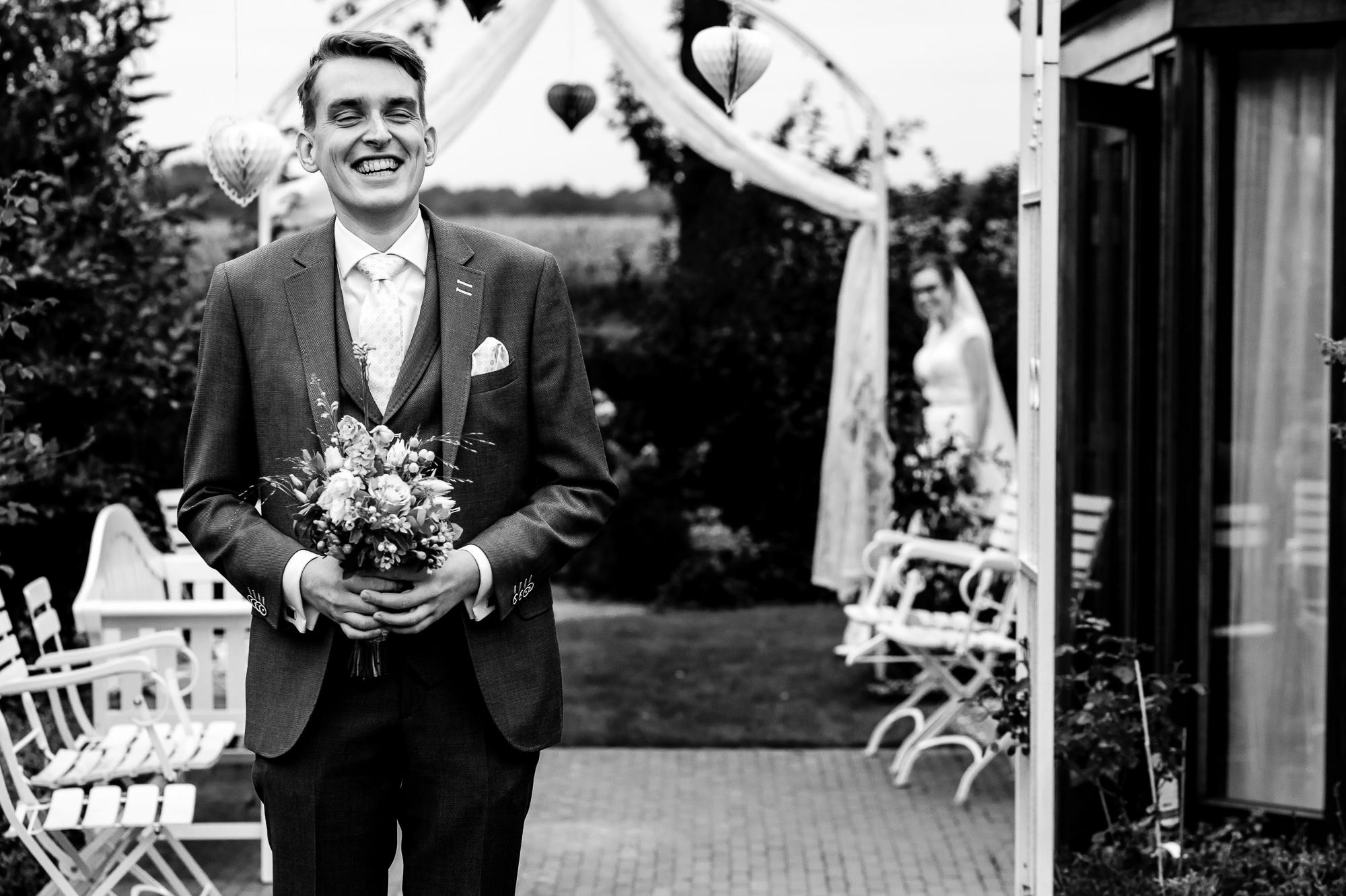 Bruidegom lacht terwijl zijn aanstaande komt aanlopen tijdens de first look