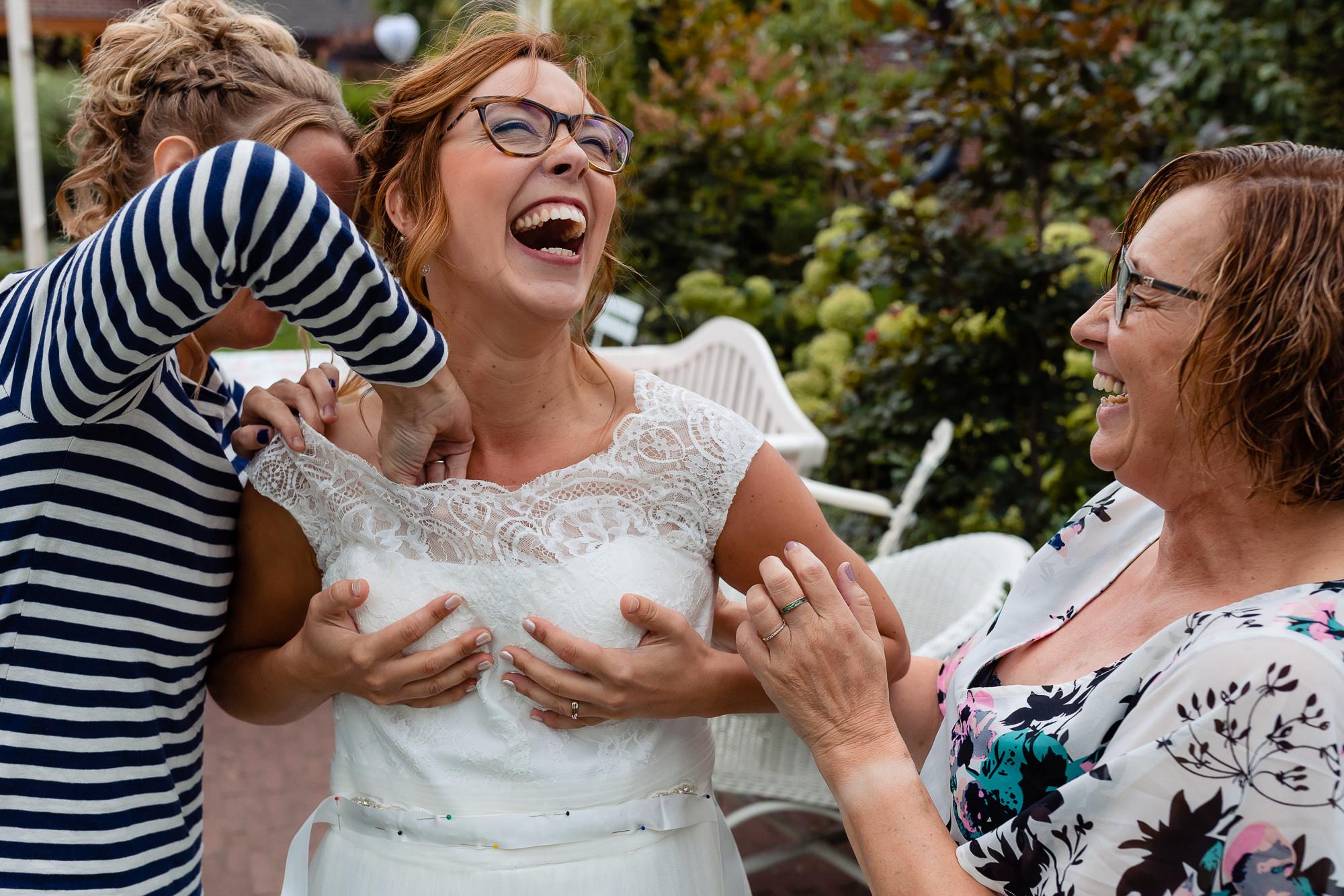 Vrouw wilt bh van de bruid goed doen en bruid barst uit in het lachen