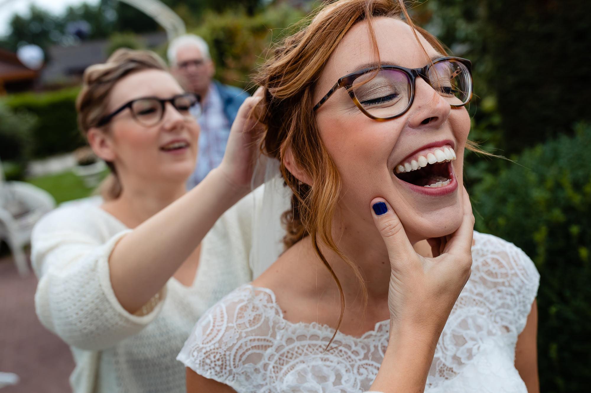 Hoofd van de bruid wordt vastgepakt terwijl de sluier in wordt gedaan en lacht