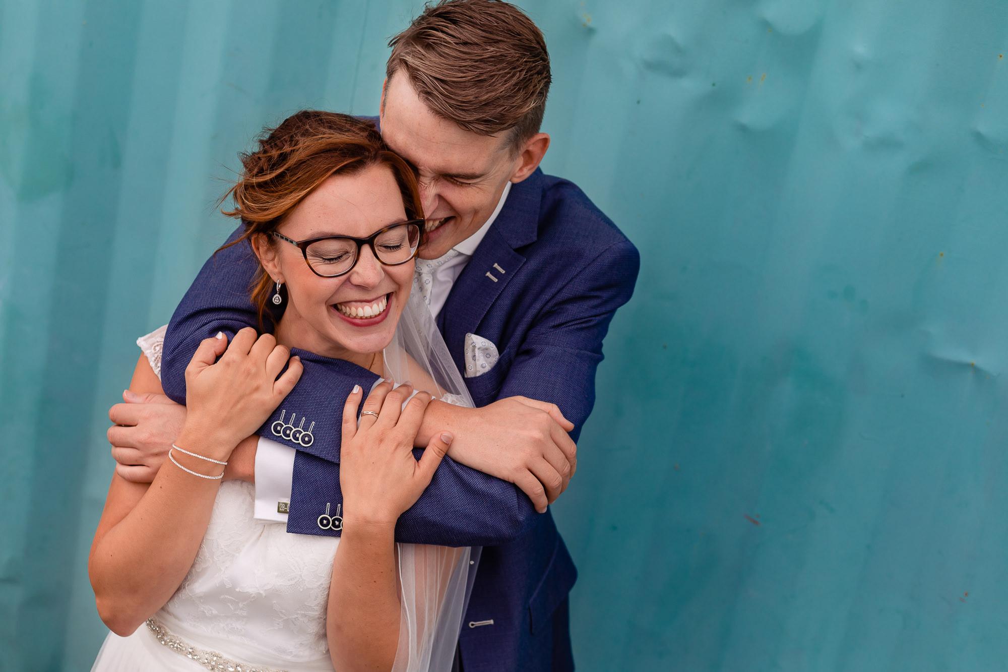 Bruidspaar knuffelend voor een blauwe container