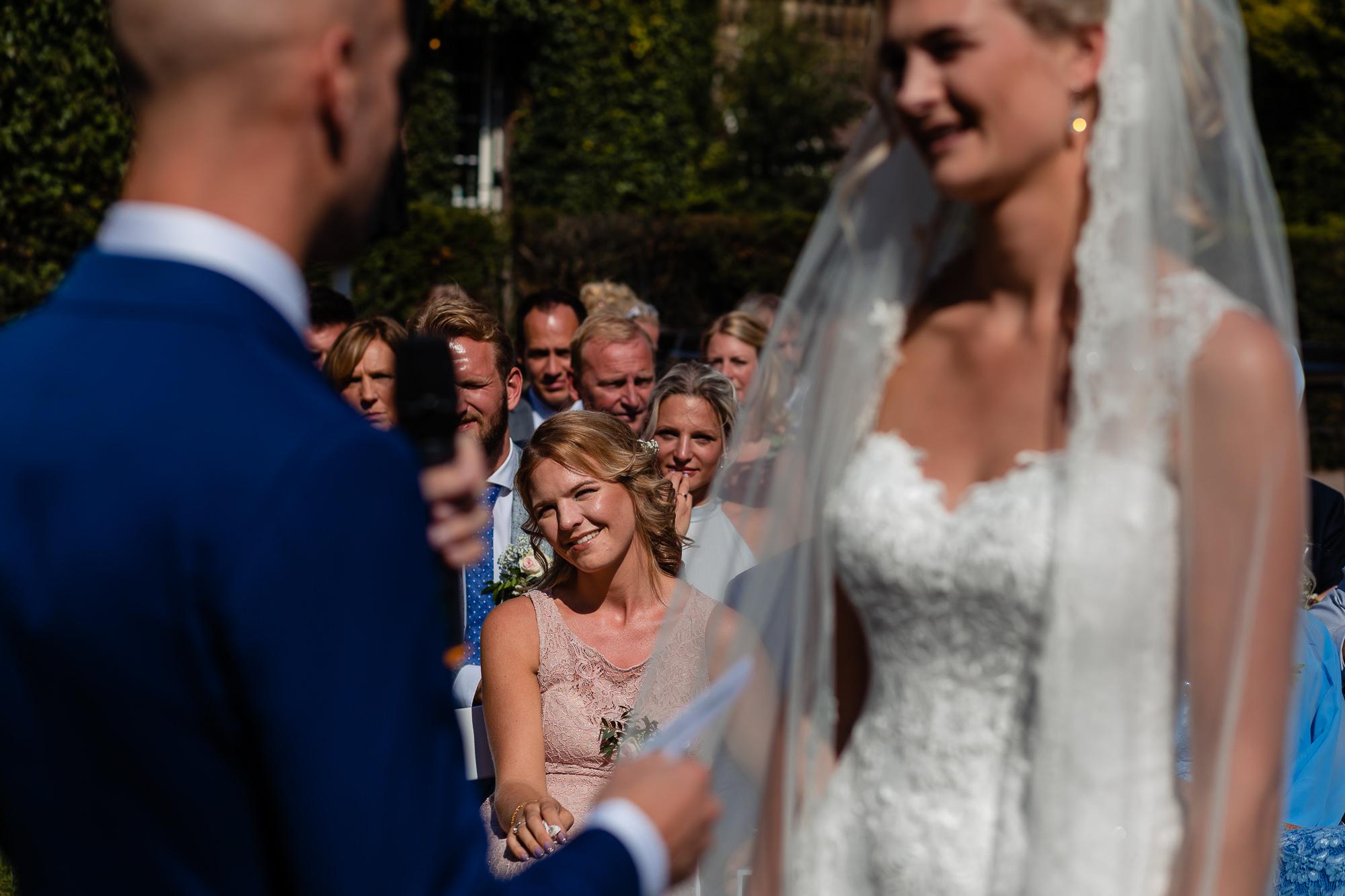 Zus kijkt vol trots naar d'r zus tijdens de trouwceremonie