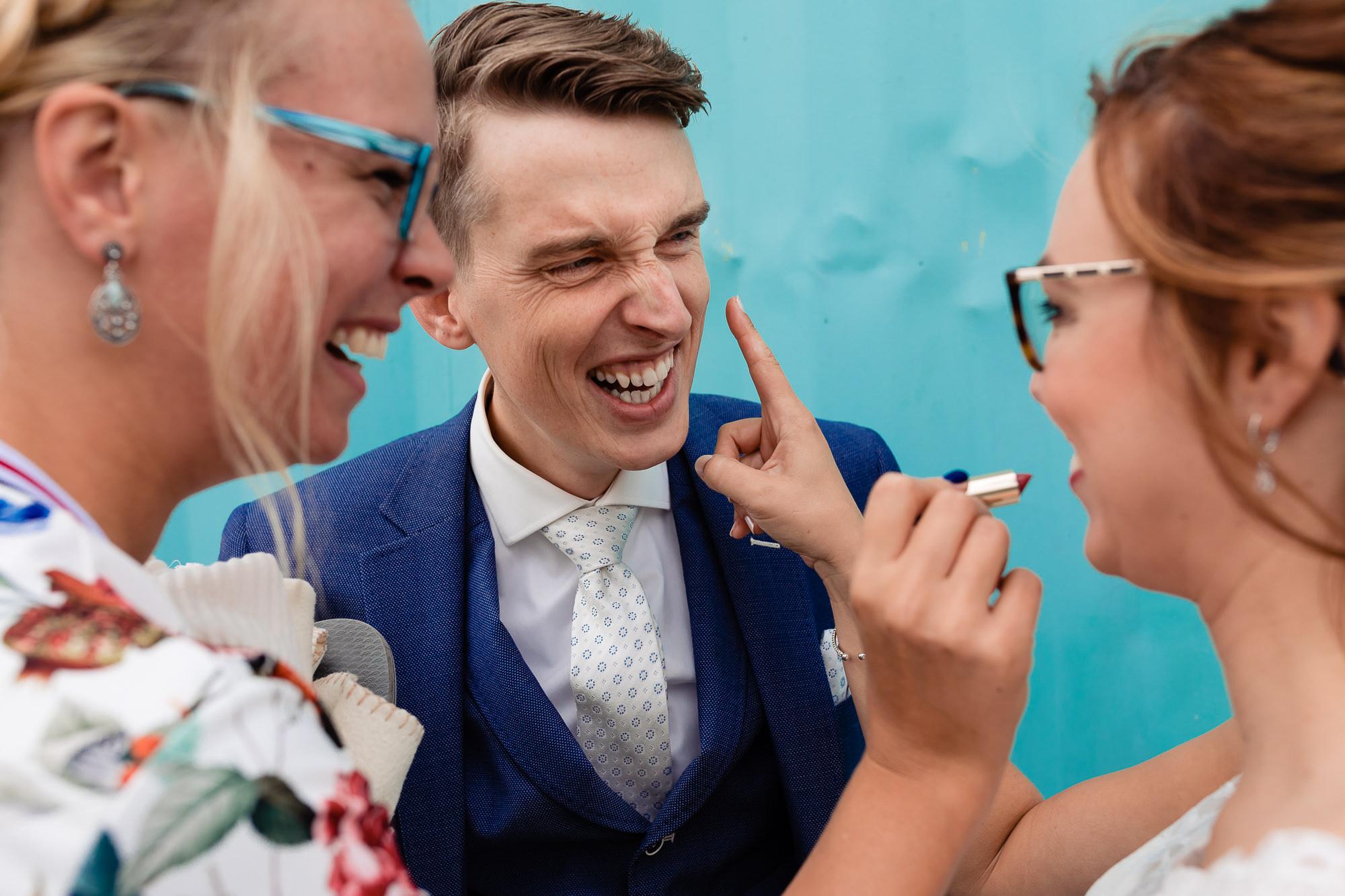 Bruid wordt opgemaakt door vriendin terwijl ze lachend de bruidegom aanraakt