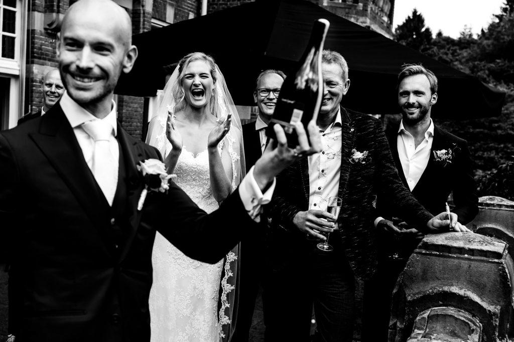 Bruidegom die de champagne heeft gesabreerd met de bruid op de achtergrond