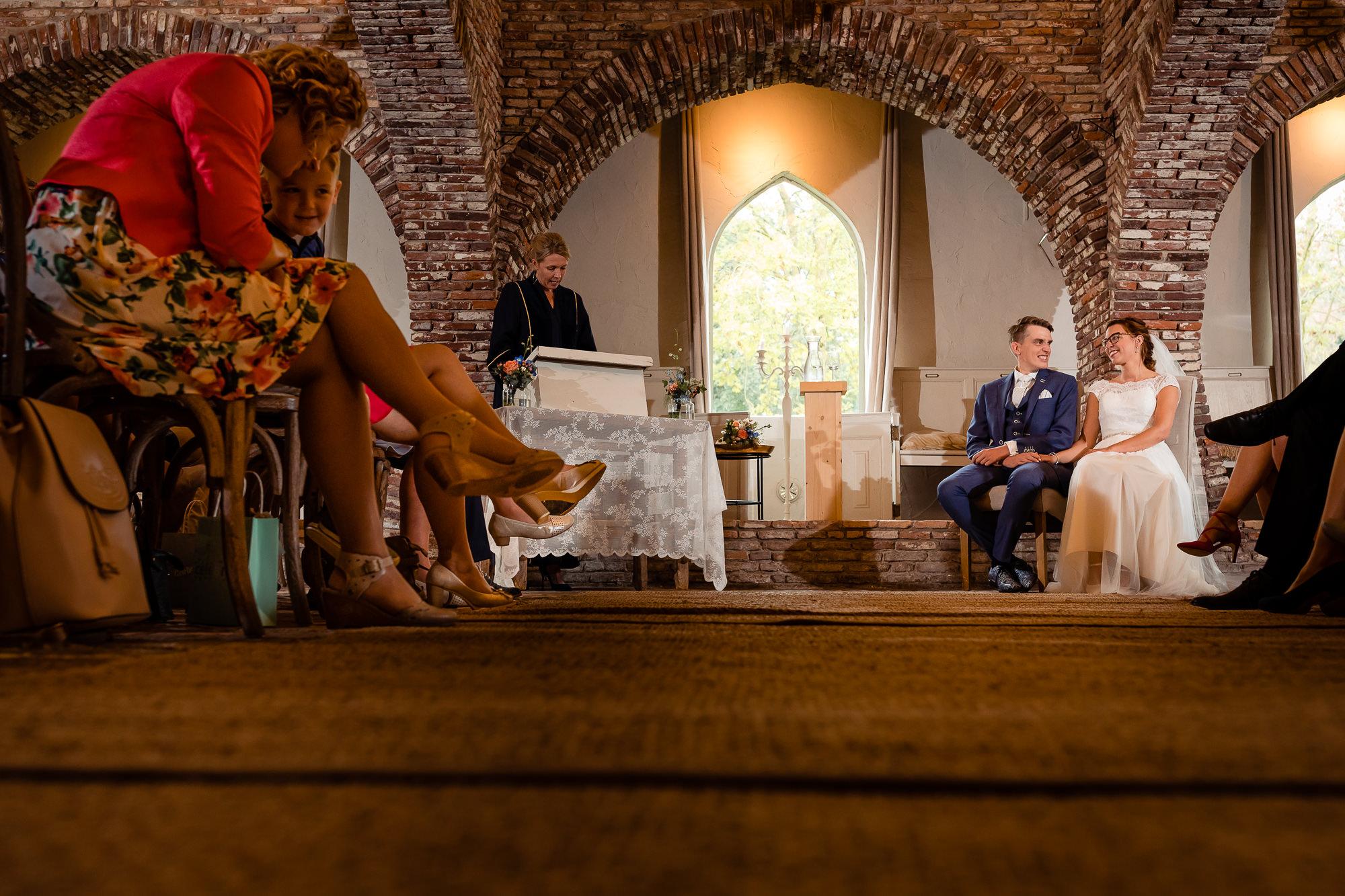 Bruidspaar zittend tijdens de trouwceremonie in Hoeve Sparrendam