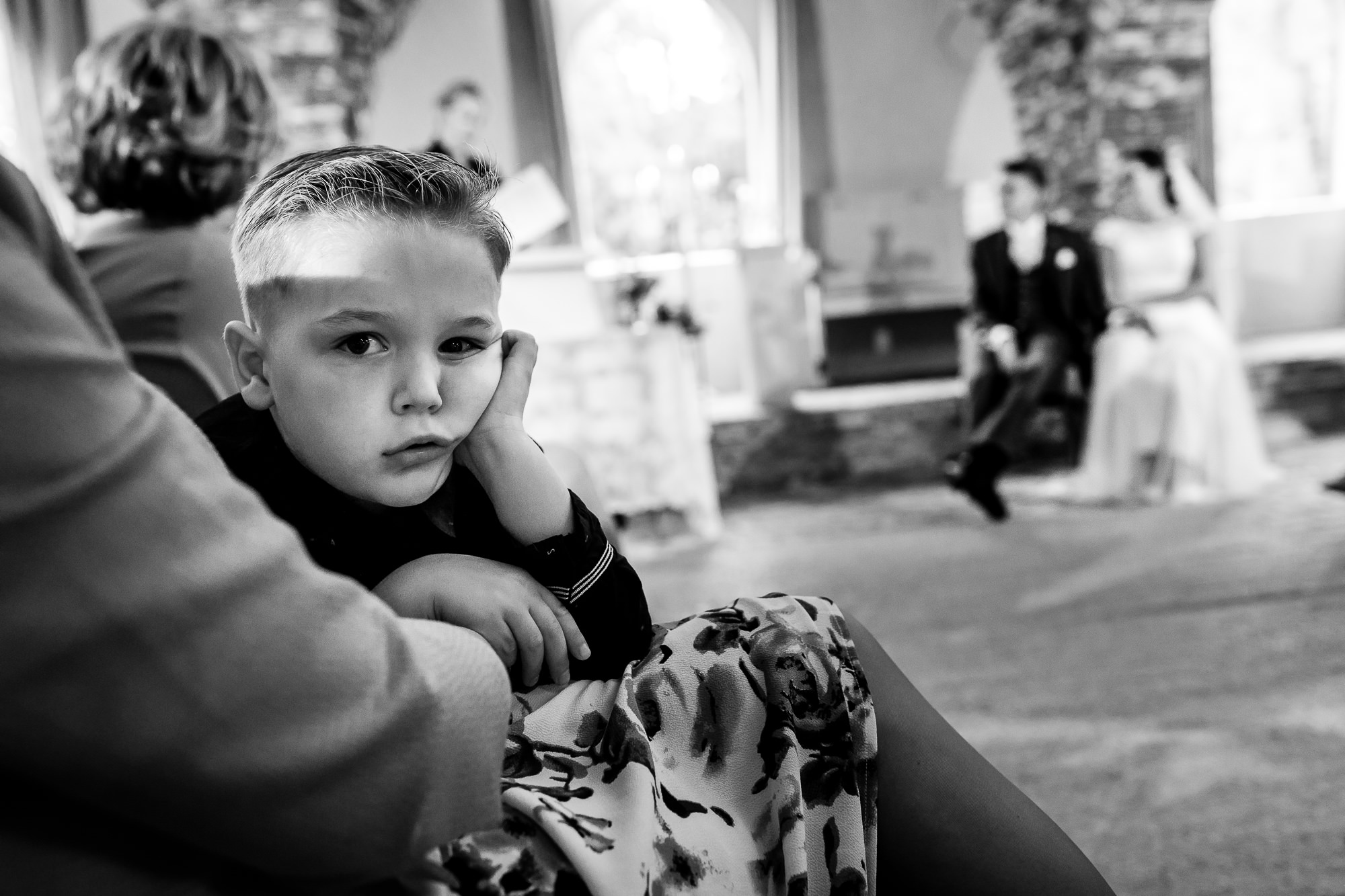 Jongetje kijkt verveelt tijdens de trouwceremonie
