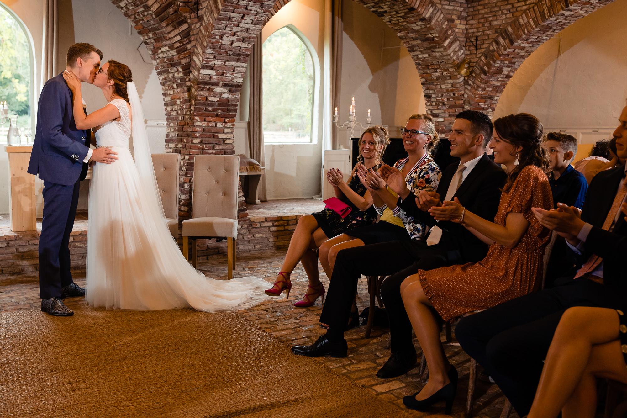 Bruidspaar kust na het jawoord tegenover vrienden en familie