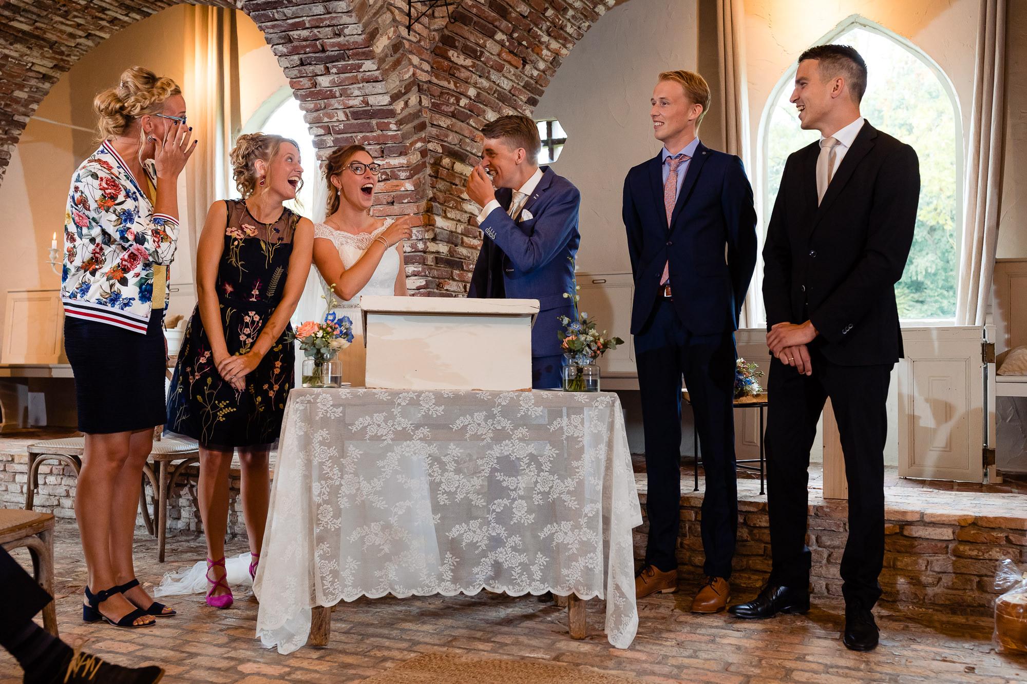 Bruidspaar lacht uitbundig tijdens het tekenen van de akte