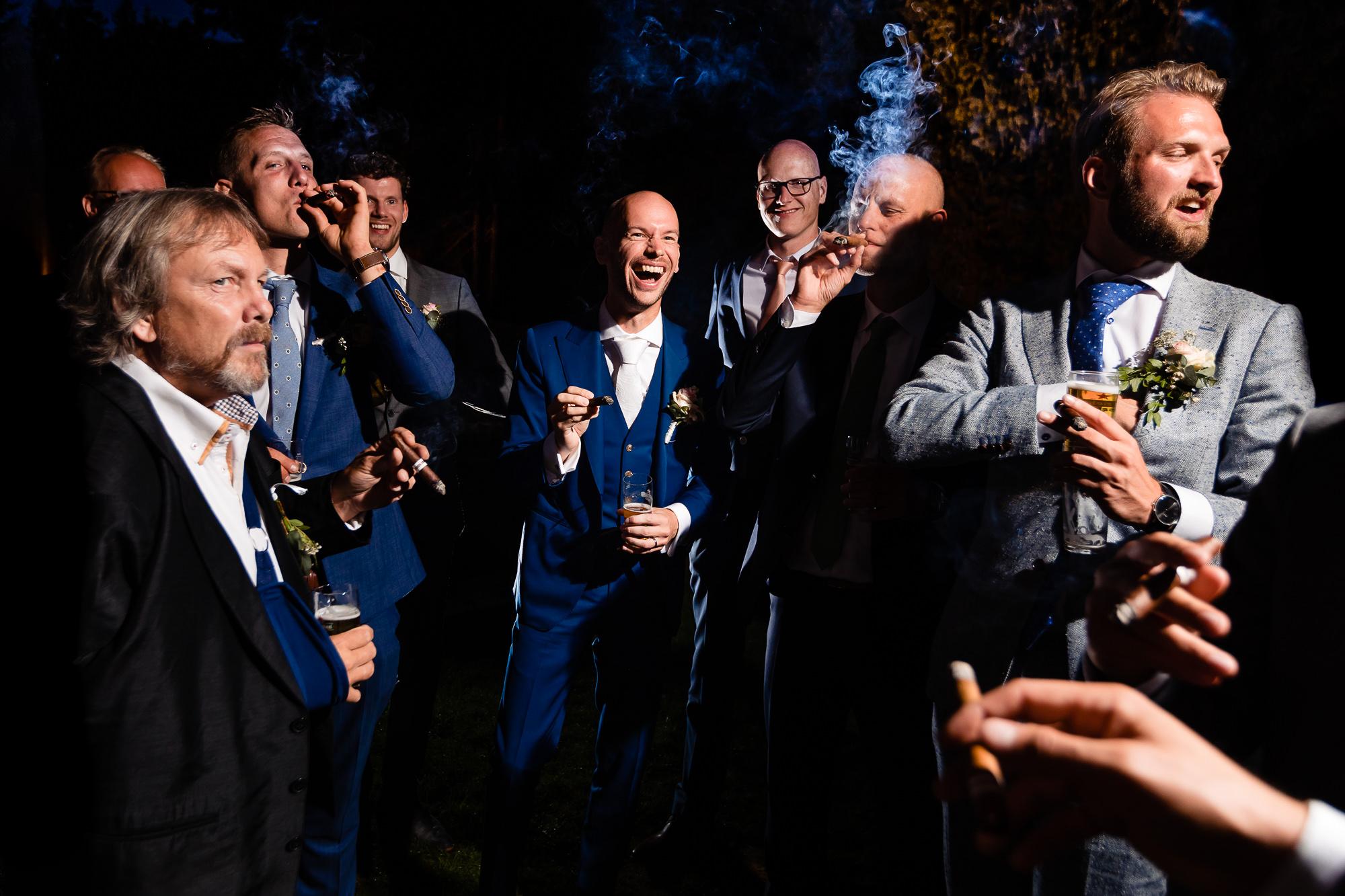 Bruidegom sigaar aan het roken samen met zijn getuigen