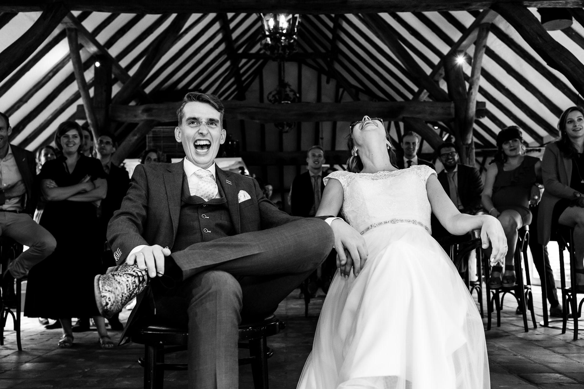 Bruidspaar lacht uitbundig tijdens een speech in Hoeve Sparrendam