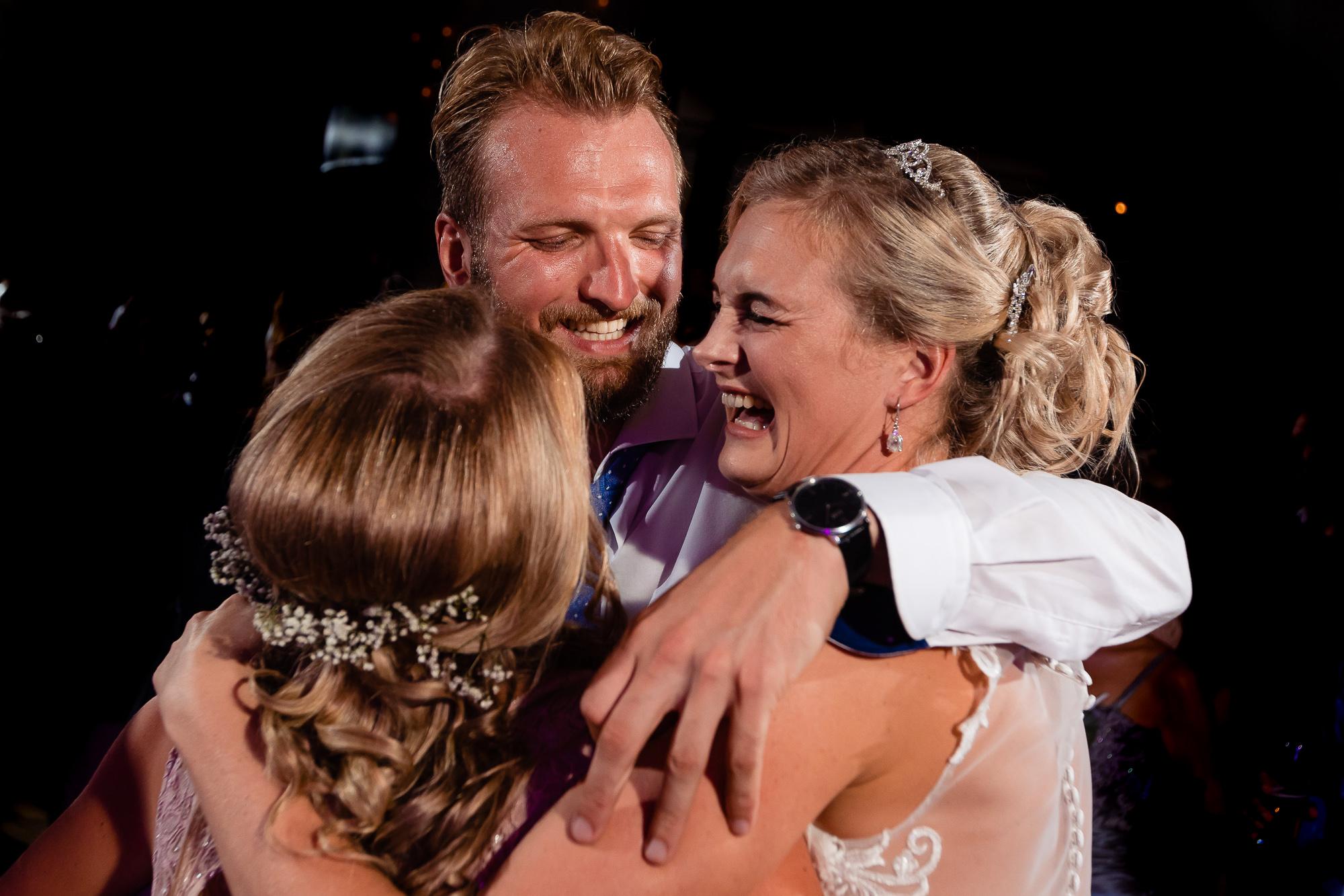 Bruid wordt geknuffeld door broer op de dansvloer