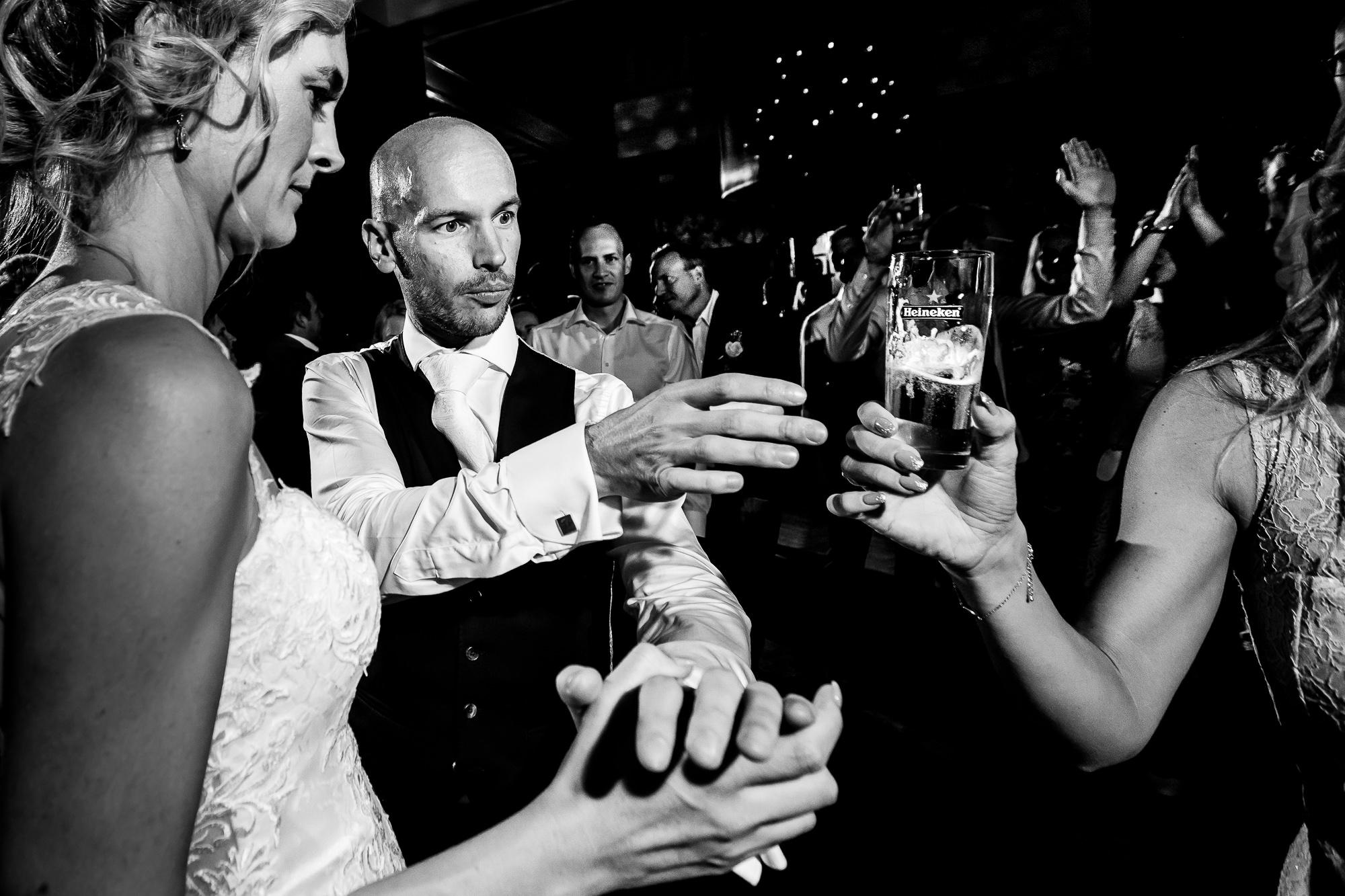 Bruidegom krijgt een biertje aangeboden en kijkt verbaasd