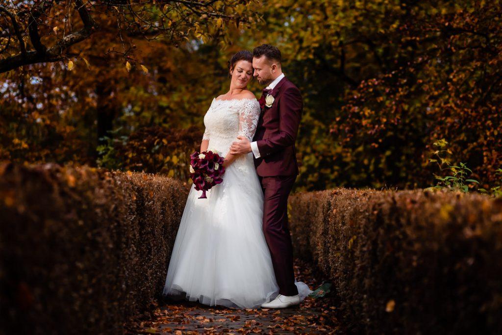 Bruidspaar poseert voor de foto met een herfst achtig achtergrond