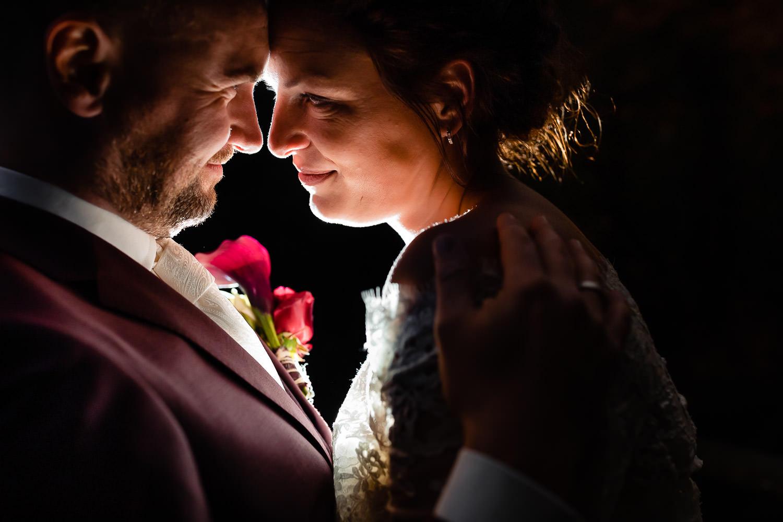 Bruidspaar staat knus tegen elkaar en wordt belicht van achter