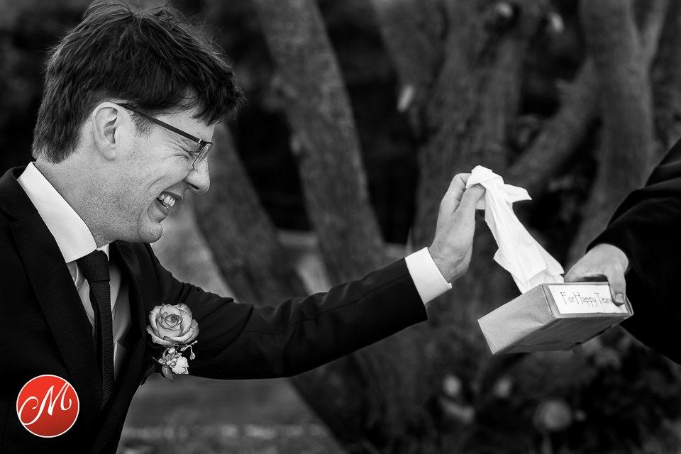 Bruidegom pakt lachend tissues met de tekst For happy tears erop