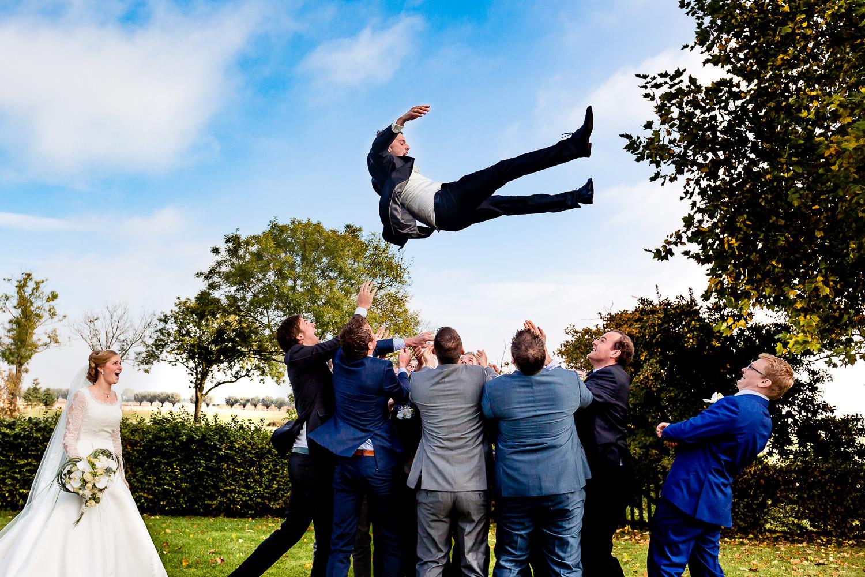 Bruidegom wordt door vrienden in de lucht gegooid terwijl de bruid toekijkt