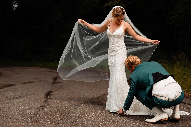 Bruidegom legt trouwjurk goed van de bruid