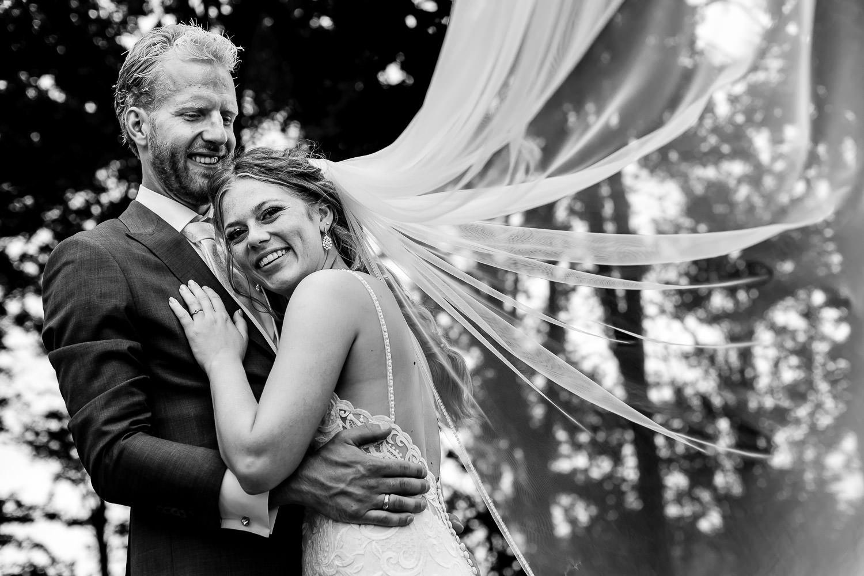 bruidspaar poseert met de sluier wapperend in de wind