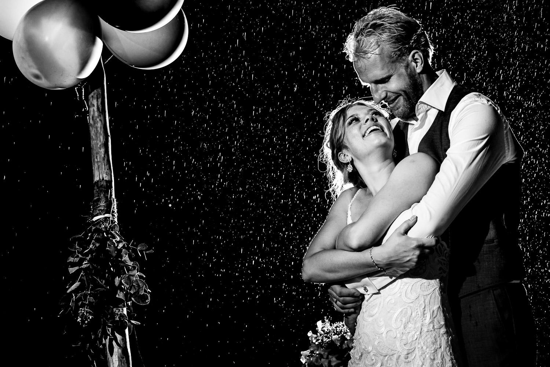 Bruidspaar knuffelend in de regen